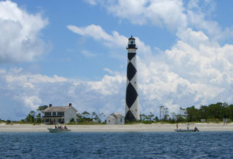 Boats glide past the Cape Lookout Lighthouse.  (NPS Photo)