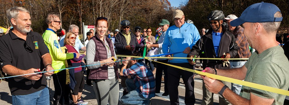 Group of men and women cutting ribbon on trail