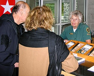 A park volunteer answers visitor questions at the information desk.