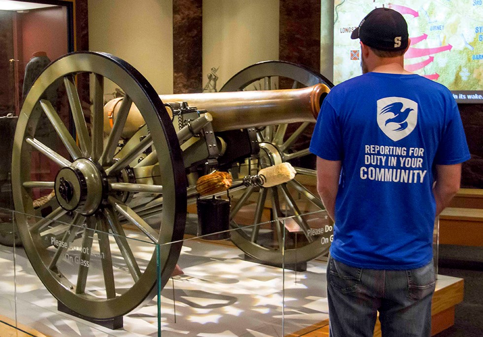 The Mission Continues: Tim Dolen visits the museum. He stands next to the cannon exhibit.