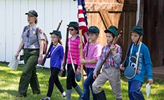 A park ranger leads five school children in a march at the Slyder farm. Four carry toy guns, one carries the U.S. flag and all are wearing green hats.