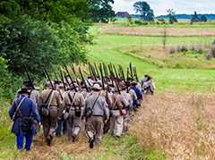 Confederate living historians march in formation on the battlefield. A red barn is in the distance.