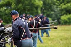 Union artillery living historians prepare to fire their cannon.