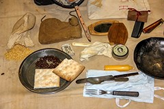 The contents of a traveling trunk include a tin plate, utensils, hardtack, candle, beans, rice, and a mirror.