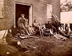 Wounded soldiers sit outside a Civil War hospital.