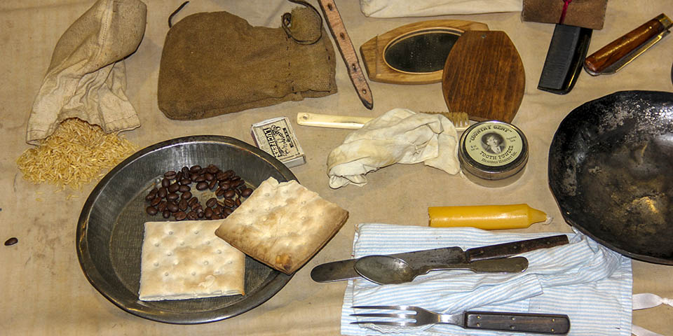 Contents of a traveling trunk include hardtack, beans, rice, eating utensils, plates, and more.
