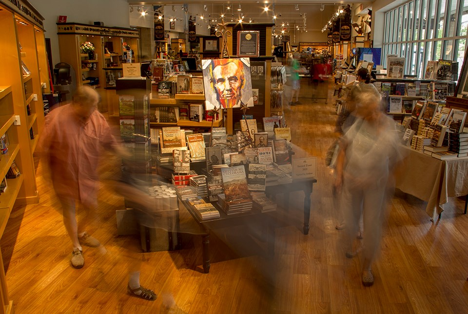 Visitors shown moving through the park bookstore. They are walking around tables of book displays and bookcases line the walls.