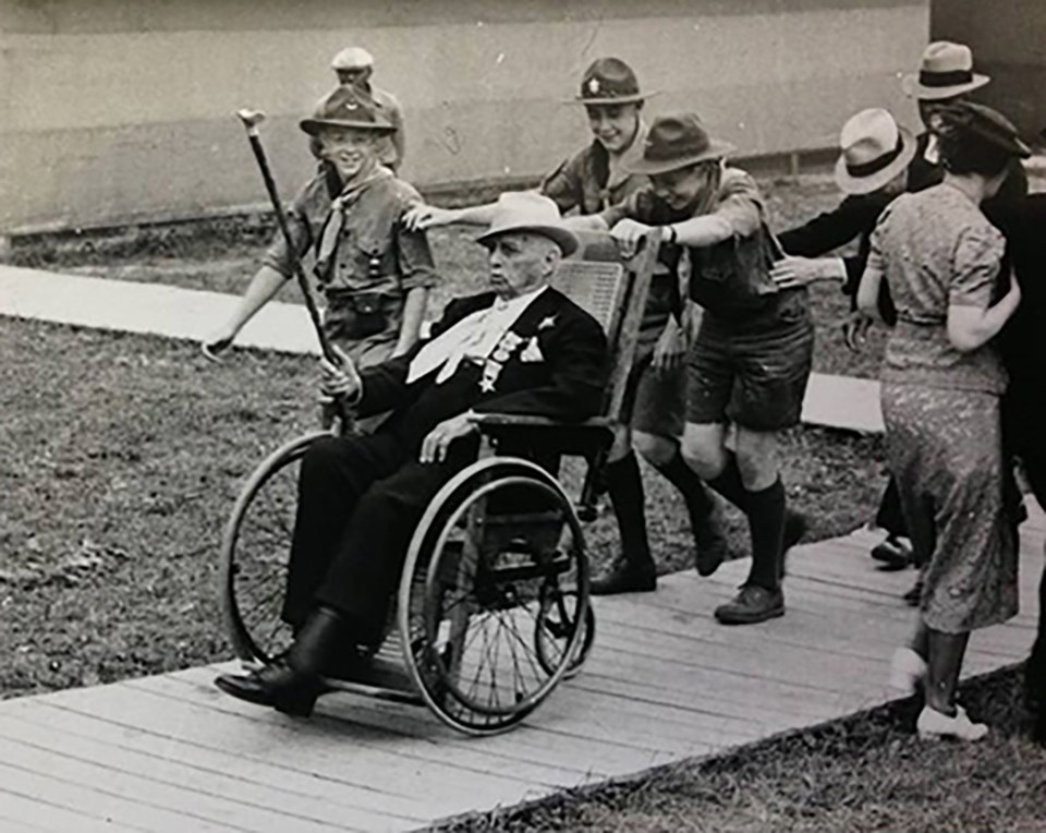 A group of boy scouts help push a veteran of the Battle of Gettysburg around in his wheel chair at the 75th Anniversary of the battle in 1938.