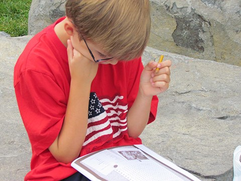A young boy, dressed in a red t-shirt with an American flag on it, reads his Junior Ranger book and answers questions.