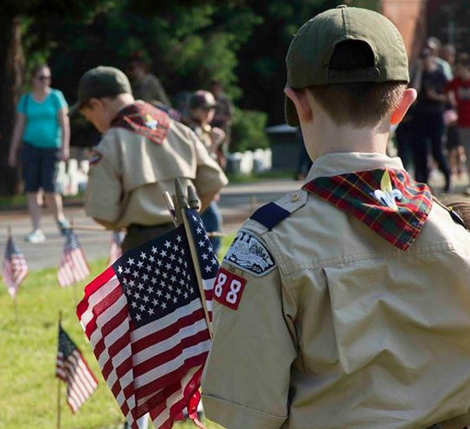 A boy scout is seen from behind as he holds a bunch of small American flags.