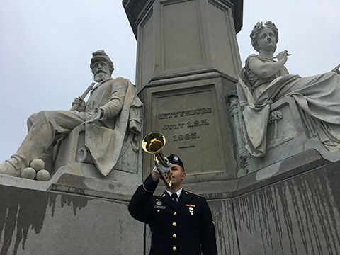 A military bugler plays Taps at the Soldiers' National Monument in the Soldiers' National Cemetery.