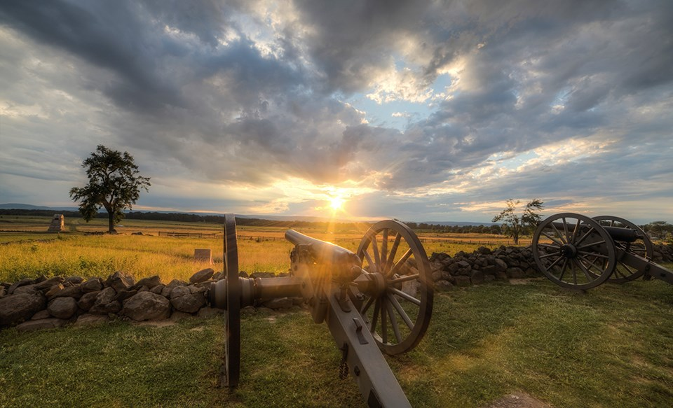 The sun sets over the battlefield. Two cannons sit in front of a stone wall and a monument and a tree are in the left distance.
