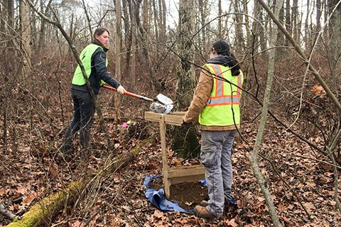 Two archaeologists conduct trail tests in the middle of the woods.