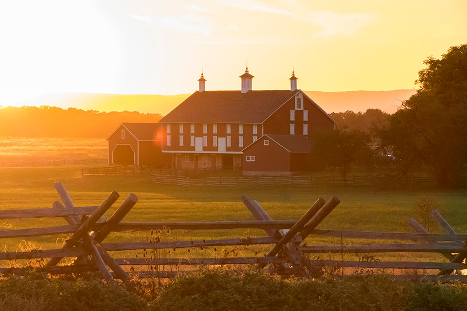 The red Codori barn is seen in front of a bright yellow sunset.