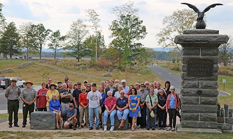 Gettysburg Foundation members and park staff pose for a group photo at the Hancock Gate along Cemetery Ridge.