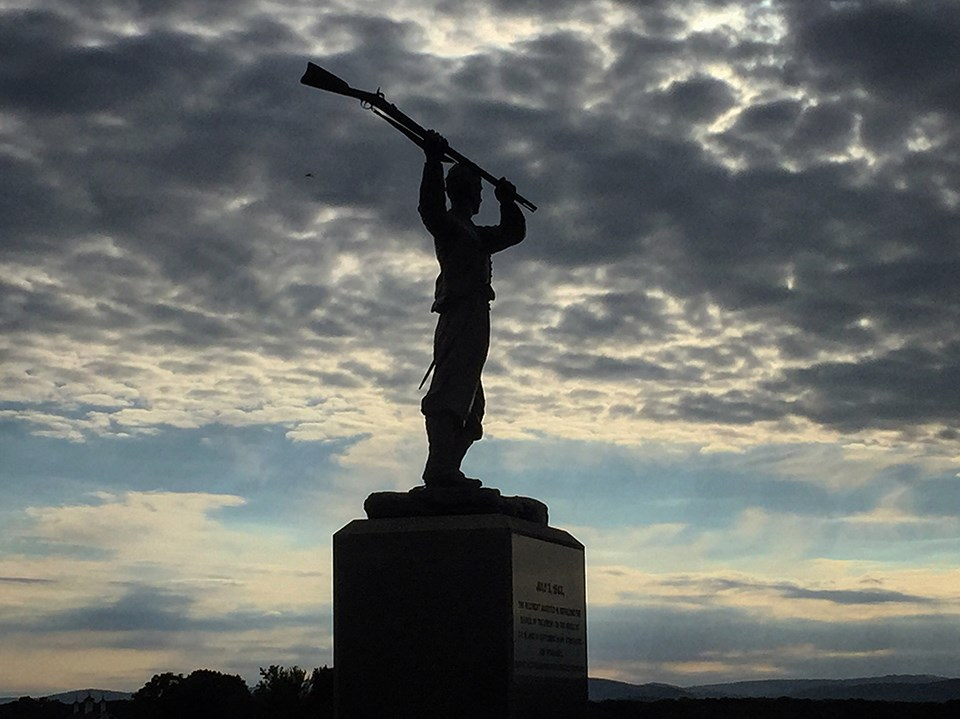 The 72nd Pennsylvania infantry monument is silhouetted against gray clouds.
