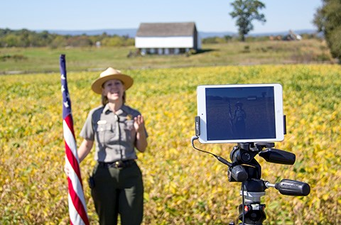 A tripod holds an iPad as a park ranger presents a virtual interpretive program via social media near the McPherson barn.