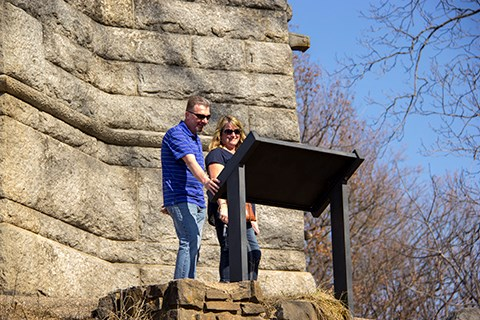 Two park visitors, one male, one female, read a wayside exhibit next to a large stone monument.