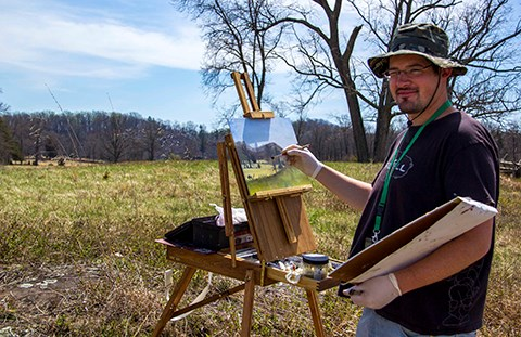 An artist paints a landscape of the battlefield. He is standing in an open field and he's using and easel.