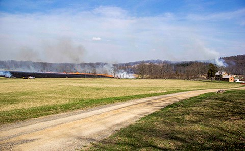 A gravel road runs from left to right across a field. In the distance a prescribed fire line has turned the field black and is burning from left to right. The Bushman house is in the lower right, well away from the prescribed fire.
