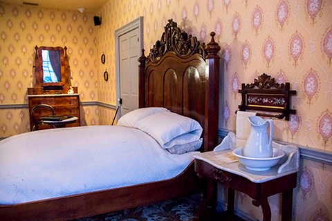 A bed with a large, ornate wooden head board sits next to the wall. On the near side is small table with a white marble top and white pitcher. On the far side is a small dresser with a mirror.