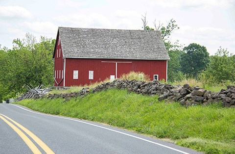 A large red barn sits to the right of a roadway and a stone wall runs parallel to the road. A row of green trees stand behind the barn.