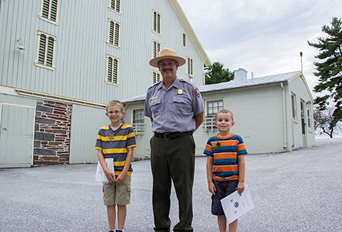 A park ranger stands with two new Junior Secret Service Agents in front of a large light green painted barn at the Eisenhower National Historic Site.
