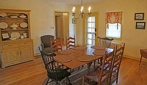 The Bushman house dining room has a table and six chairs and a hutch with dishes displayed.