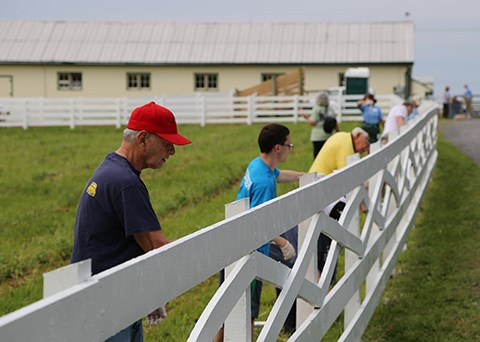 Volunteers help to paint fences at Eisenhower National Historic Site.