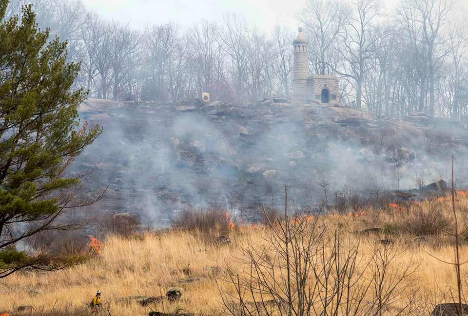 A prescribed fire on Little Round Top slowly moves from left to right down the slope of the hill. There are monuments along the top of the hill. The fire is moving through brush.