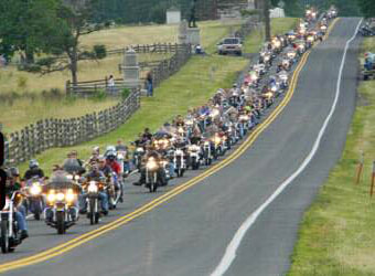 Hundreds of motorcycles drive along the Emmitsburg Road in the center of the Gettysburg battlefield.