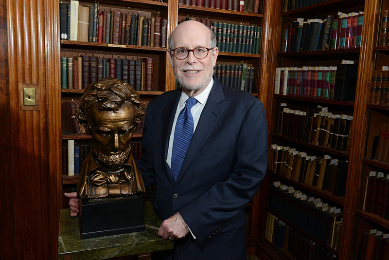 Harold Holzer stands in a library next to a bust of Abraham Lincoln.
