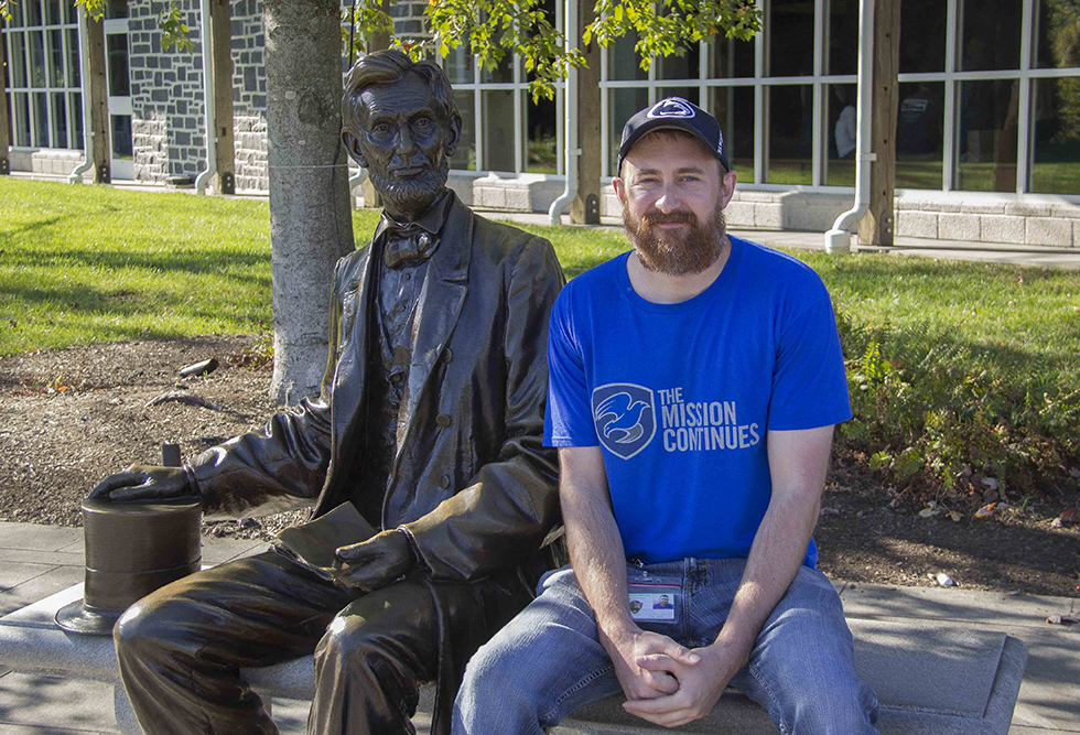 Tim Dolen, Veteran Outreach Coordinator, sits with the Abraham Lincoln statue.