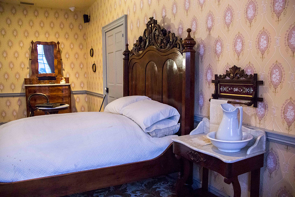 A view from the Lincoln bedroom inside the David Wills House. There is a yellow pattern wallpaper and from left to right: a mirrored dresser, a double bed with ornate headboard, and a night stand with pitcher and basin.