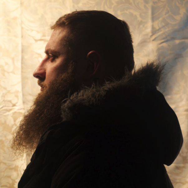 Self portrait of Joshua Osburg from his left side. He has a long beard and is wearing a dark coat with a fur lined hood.