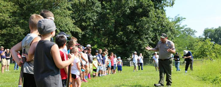 A park ranger discusses the Battle of Gettysburg with a large group of children.