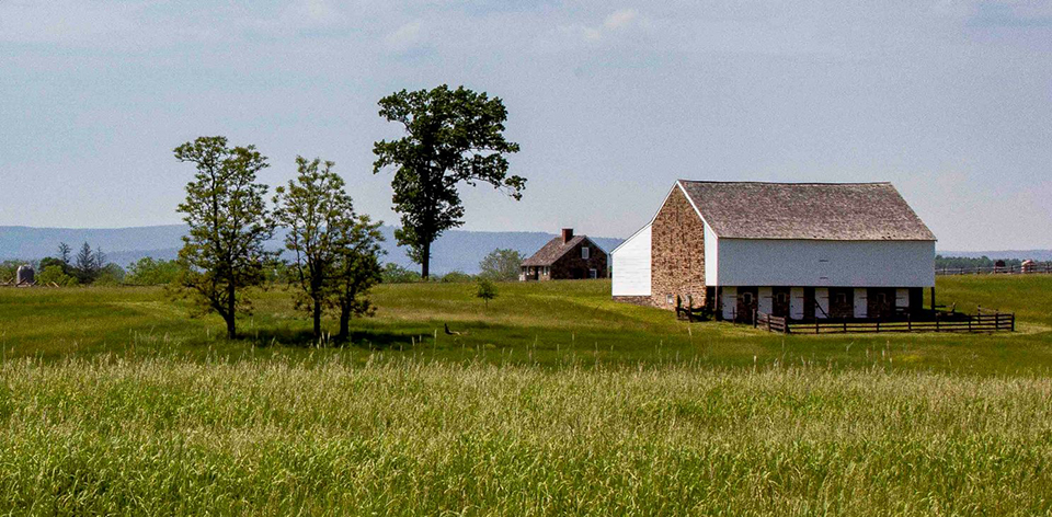 The McPherson barn, made of stone and white painted wood siding, sits on a slight ridge set among green field grasses on the right of picture. There are a few trees in the middle and another small structure in the distance.