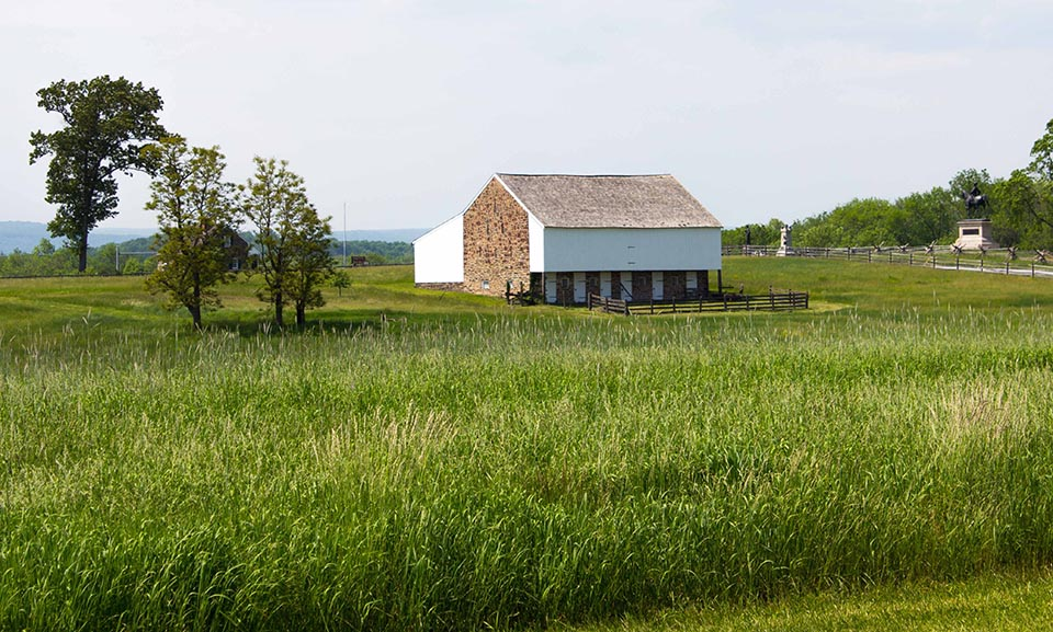 A stone and white siding clad barn stands in the middle of a green field. A few trees stand on the left and a line of trees stands on the right. Two monuments are in the distance on the right.