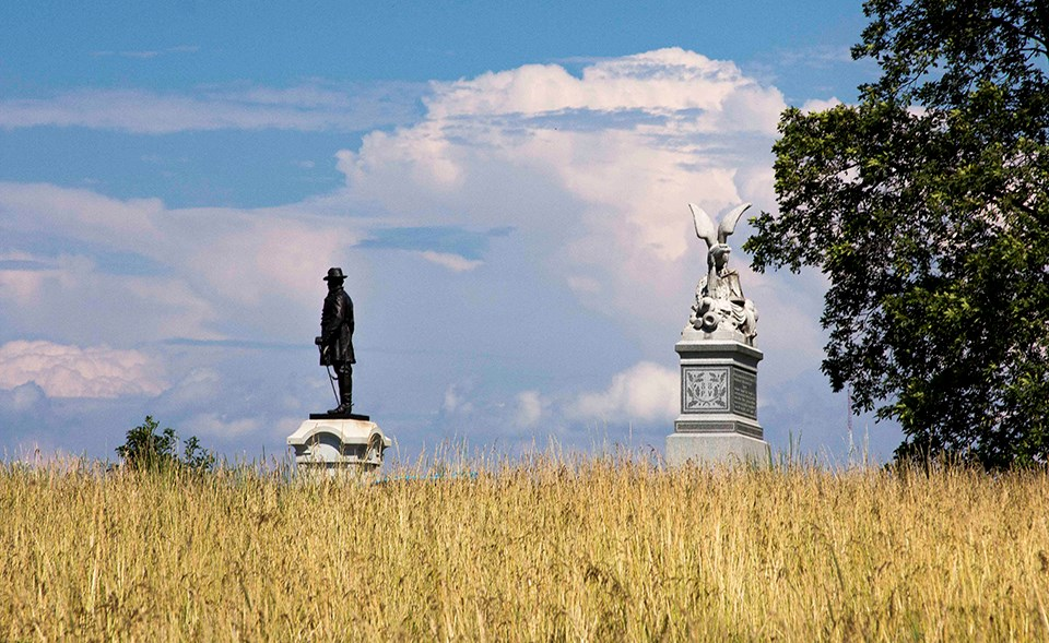 A blue sky with puffy white clouds can be seen behind two monuments at the horizon line with a wheat field in the foreground.