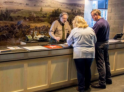 Two visitors talk with a park ranger about their visit to the battlefield.