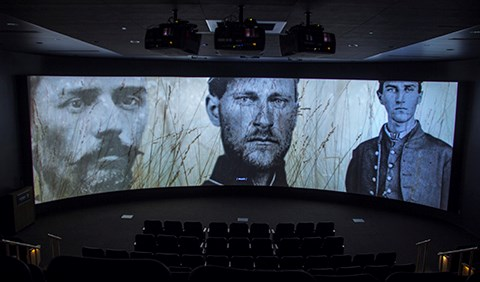 The film, A New Birth of Freedom, is playing inside the theater. The scene depicts pictures of three soldiers who fought in the battle.