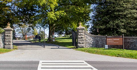 The Taneytown Road entrance into the Soldiers' National Cemetery. A black iron gate, stone wall, and entrance sign are welcome visitors.