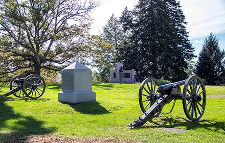 Two cannons flank the white granite obelisk monument to the 1st Massachusetts Battery.