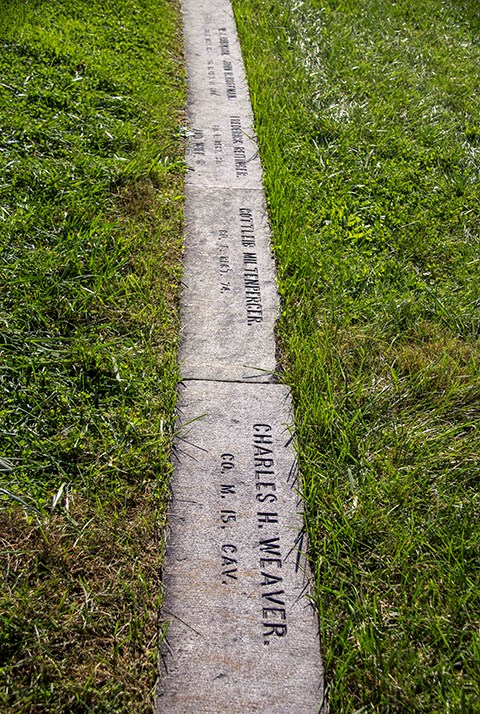 State section gravestones are nearly at ground level and include the soldier's name, rank, and unit.