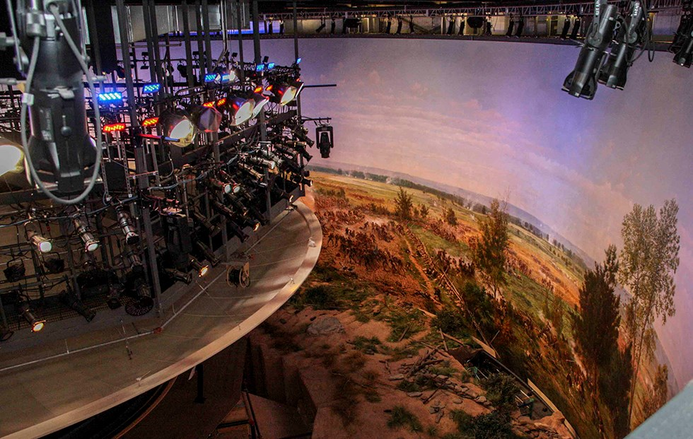 The Cyclorama painting as seen from above. Numerous colorful lights are above on the left, the painting curves around from right to left, and a large diorama is in the center.
