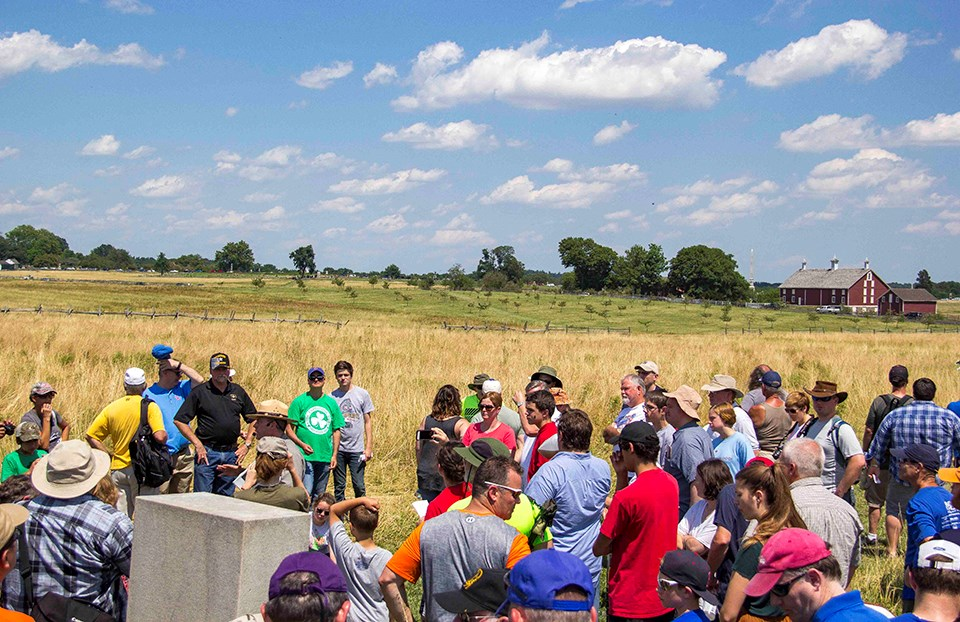 A large group of visitors gather around a park ranger during a Pickett's Charge battle anniversary program. The group stands in an open field of yellow grass and in the distance is a line of trees and a large red barn under a blue sky with a few clouds.