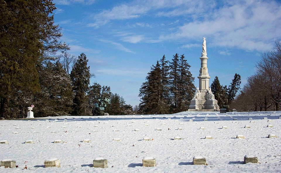 Snow covers the ground in the National Cemetery. The Soldiers' National Monument stands against a blue sky.