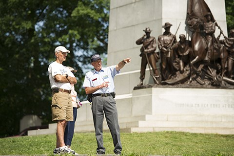 A Licensed Battlefield Guide gives a tour of the battlefield at the Virginia memorial. One guide and two visitors stand near the Virginia memorial.