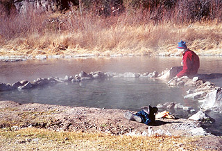 A photo of a visitor enjoying the hot springs at Lightfeather Hot Spring in December