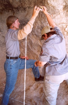 A photo of archeologists measuring the side of a cave wall.